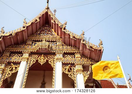 Traditional golden Thai Buddhist temple with carved ornaments and yellow Buddhist flag. Asian religious landmark against the sky. Wat Chaimongkhon Royal Monastery in Pattaya Thailand