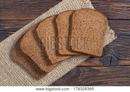 Slices of black rye bread on dark wooden table top view