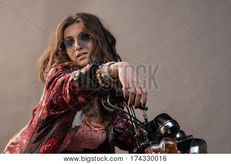 A sexy girl sit on a bike with hands on the handlebar long blonde hair and sunglass