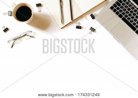 Modern minimalistic work place. White office desk table with laptop, coffee cup, glasses, clips, notebook, pen and penclil. Top view with copy space, flat lay
