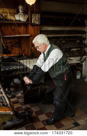 IRONBRIDGE UK - CIRCA 2013: A man in period costume works a traditional printing press at Blists Hill Victorian Museum Shropshire UK