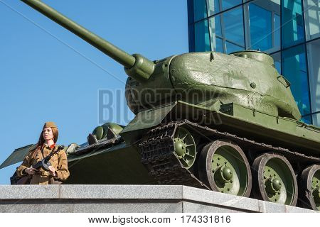 A girl in soviet uniform posing near an armored tank in Constitution square in Kharkiv Ukraine