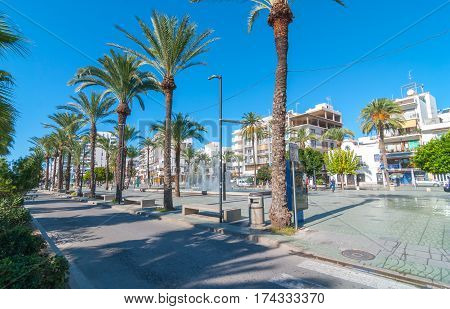 Sant Antoni De Portmany, Ibiza, November 6th, 2013:   Tourism in Spain.  Bright morning sunshine on town square pedestrian park & fountain.  Palm tree lined street. Man on a bicycle.  People outdoors.