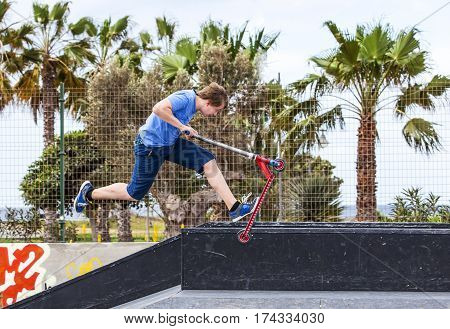Boy Rides His Scooter At The Skate Park