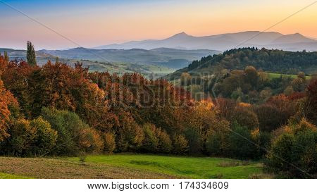 Sunset Over Autumn Forest In Hazy Mountains