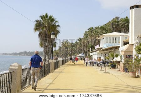 MARBELLA, SPAIN - FEBRUARY 26, 2017: People walking by the sand promenade in the town of Marbella Andalusia Spain