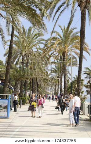 MARBELLA, SPAIN - FEBRUARY 26, 2017: People walking by the promenade along the Mediterranean sea in Marbella Andalusia Spain