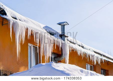 In the winter icicles are hanging on a building roof sunshine