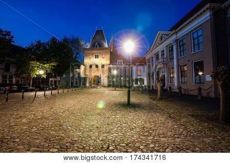 KAMPEN, NETHERLANDS - December 10, 2016: old medieval city gate: Koornmarktpoort with square. photo made at night with long exposure. Kampen, Overijssel - Netherlands.