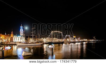 Overlooking the city front and the quay of the city of Kampen at the river IJssel.  Long Exposure photography with just lighted boats along the quay. Overijssel - Netherlands.