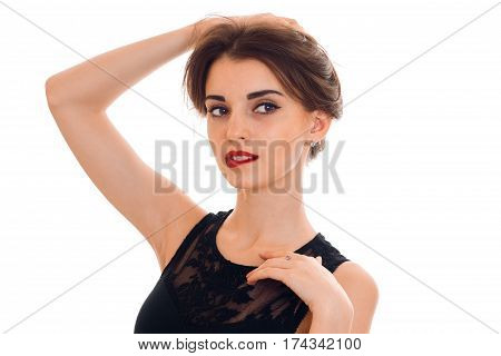 Portrait of a charming young girl with red lipstick on lips which raised a hand to hair close-up