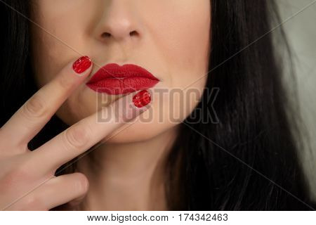 Beautiful young woman with red hand nails.