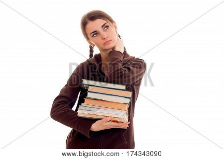 Teen girl with pigtails in the jacket looks up and holds a lot of books isolated on white background
