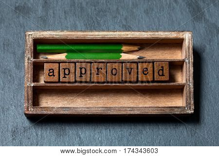 Approved and accepted symbolic concept. Vintage box, wooden cubes with old style letters, green pencils. Gray stone textured background. macro, up view