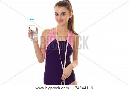 young beautiful slender girl in body bathing suit holding a bottle of water and a measuring tape on the neck is isolated on a white background.