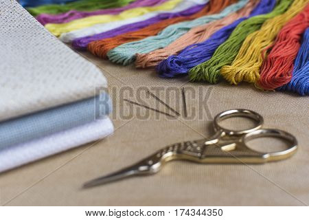 Embroidery and cross-stitch kit on a natural linen background. Focus on the multicoloured threads.