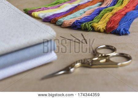Cross-stitch set for embroidery consisting of canvas needles threads and scissors. Focus on the colourful threads.