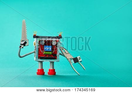 Handsaw pliers serviceman robot on cyan paper background. Funny toy handyman character with metallic repair hardware. Copy space.