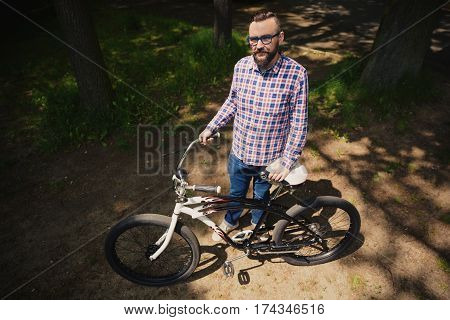 Young Modern Man Standing At Park Holding Bicycle Handlebar