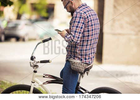 Young Man Sitting On Bike Using Mobile