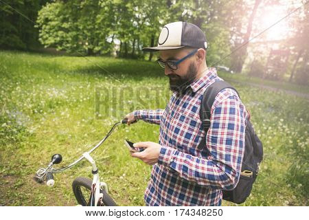Hipster Man Holding Handlebar And Using Mobile Outside