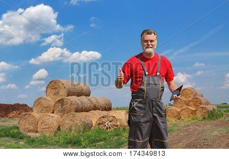 Smiling farmer in hay field with bale gesturing with thumb up and tablet in other hand