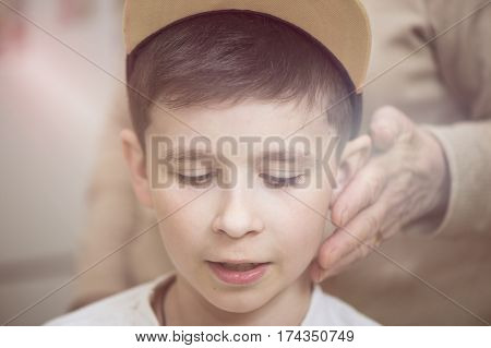 Grandmother's hand strokes the boy's face. Grandmother and grandson. The concept of the family
