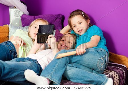 Three children � sisters - playing video games in their room
