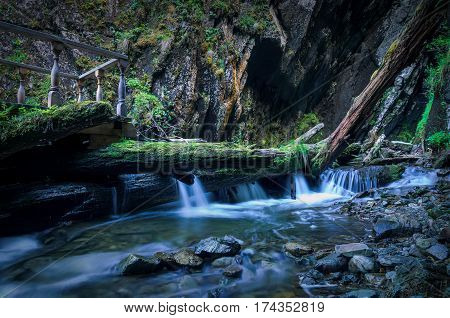 small waterfall that flows from the tree on the rocks. waterfall is located in a forest in Russia