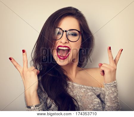 Young Happy Female Woman In Glasses With Open Wide Mouth Showing Rock V-sigh Gesture On Blue Backgro