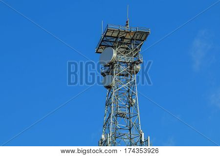 communications tower Antenna tower against sunburst. Smart phone repeater equipment expanding 4G signal coverage with cloudy blue sky and sunflare background