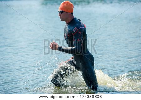 Triathlon Cup of Ukraine and Cup of Bila TserkvaTriathlon Cup of Ukraine and Cup of Bila Tserkva. July 24 2016 in Bila Tserkva.Triathlete running out of the water on triathlon race.