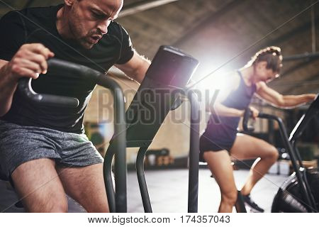 Man And Woman Riding Cycling Machines Grimacing