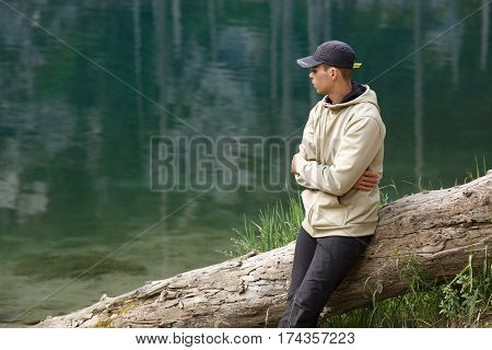 Young man sitting on the shore of a mountain lake