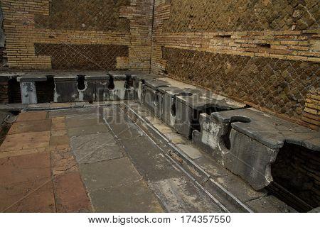 Roman public lavatories at Ostia Antica roman city. Rome in Italy.