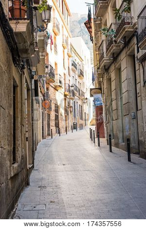 Narrow streets with medeival architecture in Alicante old town historic district Santa Cruz on the way to Santa Barbara mountain paved path