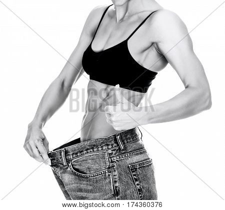 No more fat! Woman in big jeans, isolated on white