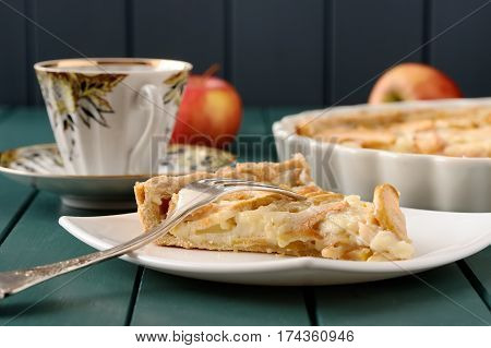 Apple tart with cup of tea and three whole apples close up