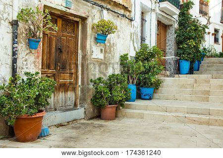 Old residential houses in medieval style with wood doors terracota and blue flowerpots staircase Alicante Santa Cruz historic district