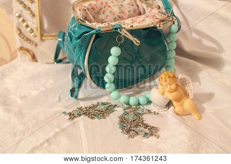 lady's accessories turquoise color purse with beads, silver earrings and little sleep angle beautify for home