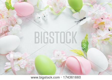 Beautiful delicate Easter frame with pink cherry flowers multicolored Easter eggs Easter bunny and butterfly on the stone background with copy-space