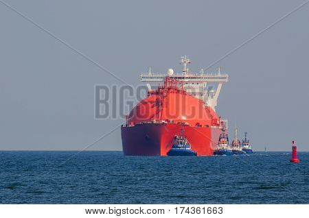 RED TANKER AT SEA - LNG tanker at sea with the assistance of tugs