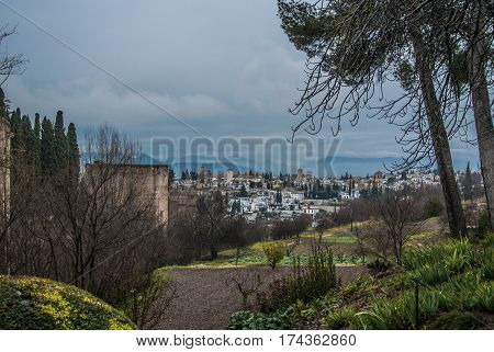 GRANADA SPAIN - FEBRUARY 10 2015: A view to Granada city and towers of a castle of Granada on winter rainy cloudy day Andalusia Granada Spain.