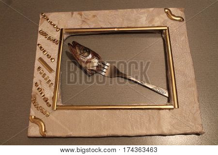 head of marine fish prick on fork lay in white frame