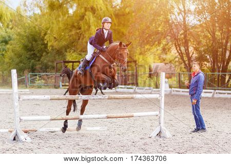 Young horseback sportswoman jumping over obstacles on show jumping training with trainer