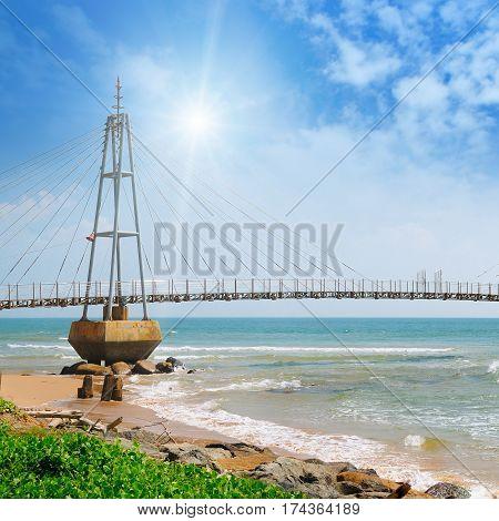 The bridge to the island the ocean and the sun in the blue sky (Matara Sri Lanka)