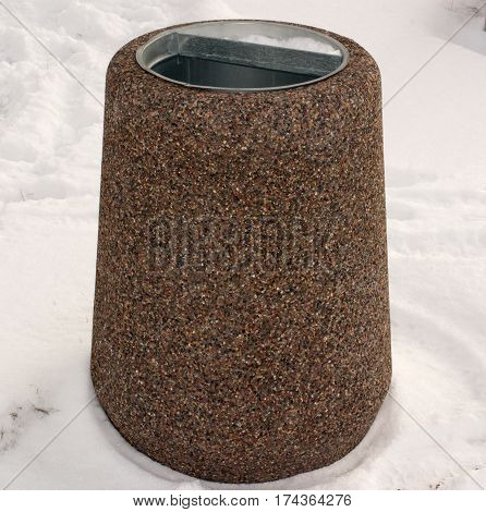 Dustbin of granite in the snow. Urban landscaping.