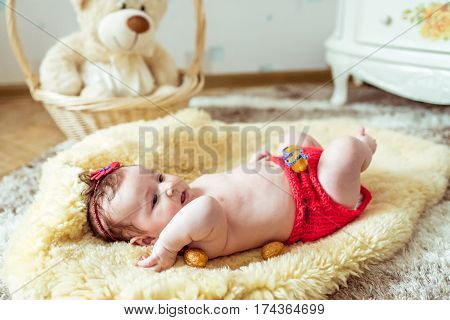 naked baby lying on a yellow soft coverlet with decorated golden nuts in the room