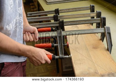 Carpenter presses glued wooden board with a screw clamp - close-up