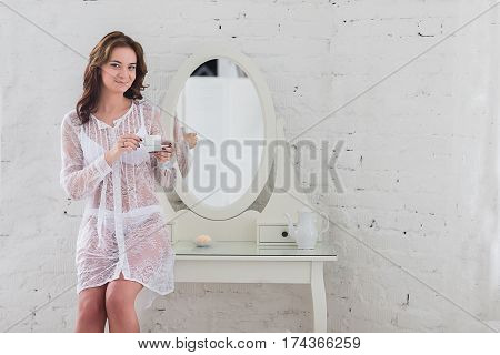 Morning coffee in the hands of an attractive young woman in delicate lingerie.